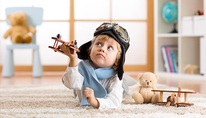 Photo d'un enfant qui joue avec un avion en bois
