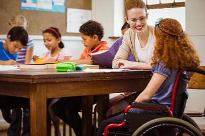 Photo d'un enfant en classe en fauteuil roulant avec une éducatrice spécialisée